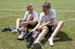 Girls lacing up soccer cleats outdoors.jpg